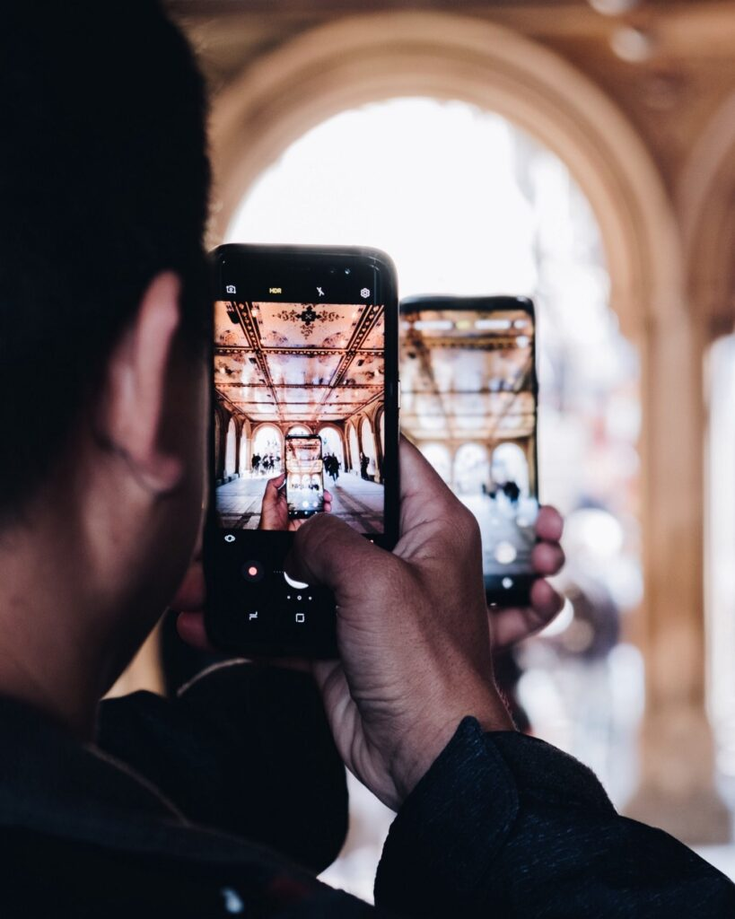Man holding two phones taking picture in picture image